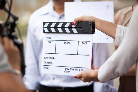 Weibliche Hände der Filmcrew, die Filmklappe im Filmset halten Standard-Bild
