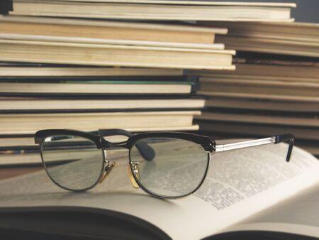 Old eyeglasses on books. Blurred letters