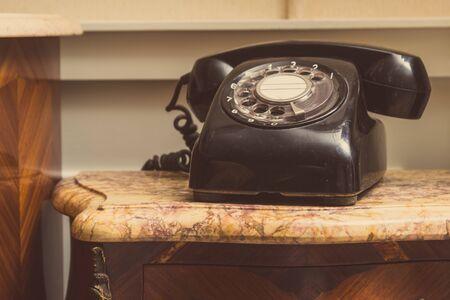 Oude zwarte telefoon op kruk Stockfoto