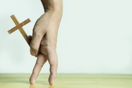 Hand holding wooden cross with finger in walking gesture
