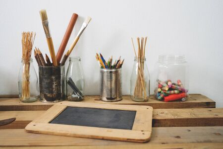Small chalkboard on wooden table with painting tools in the background against the white wall Imagens