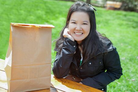 Smiling happily Asian young girl with paper shopping sag on table with green grass background Stock fotó