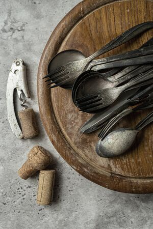 Utensils on wooden platter and wine opener on the side Stock fotó