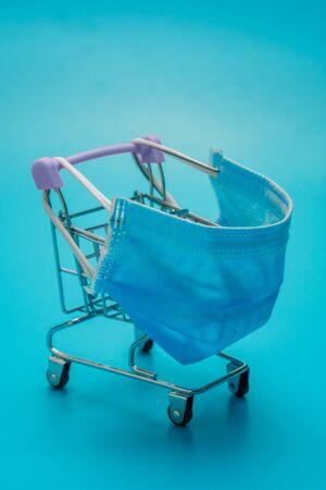 Shopping trolley wearing mask on blue background Stock fotó