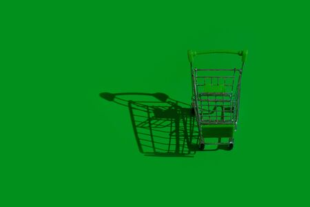 Shopping trolley on green background with harsh shadow cast on the ground