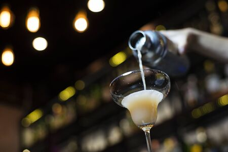 Bartender pouring coctail, selective focus with bokeh background