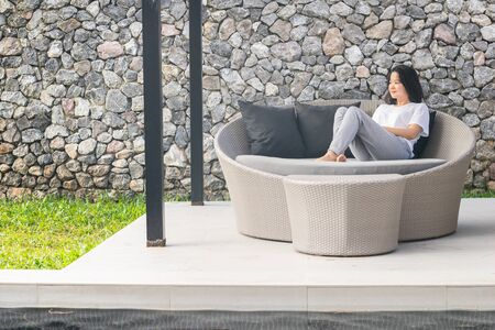 Asian female lady relaxing on round sofa with stone wall in the background Stock fotó