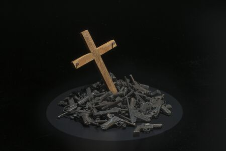 Wooden cross in the pile of guns with dark environment