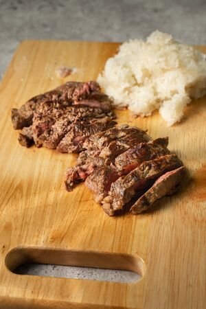Wagyu beef steak with sticky rice on wooden cutting board