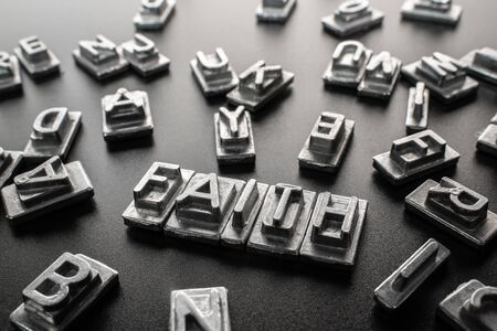 The word FAITH formed by metal stamp letters Stock fotó