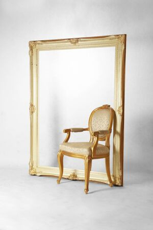 Large vintage picture frame and luxury chair in empty grungy white background