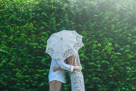Asian couple kissing behind umbrella Stock fotó