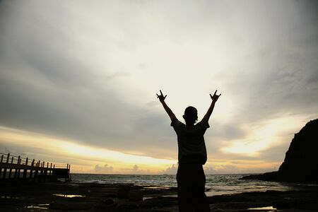 Silhouette of man holding up his hands and finger gesture to the sea