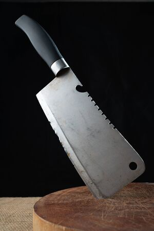 Old cleaver on wooden cutting board