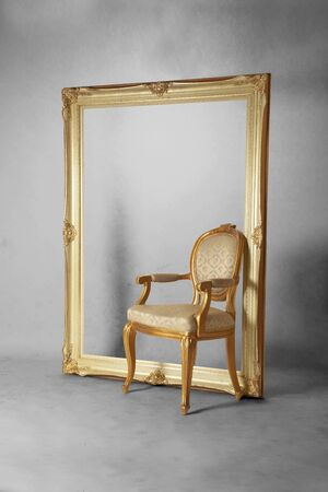 Luxurious chair and large photograph frame in dirty gray room Standard-Bild
