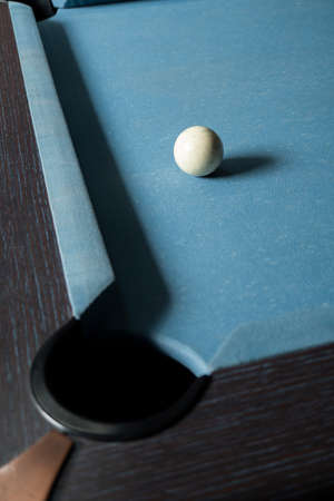 Pool table with old white ball near the hole Reklamní fotografie