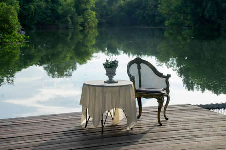 Tea table and luxury old wooden chair by the river Stock fotó