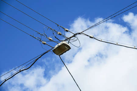 Power lines and lamp on sky background