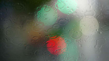 Raindrops on the windshield of the car with a bokeh light background