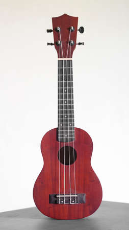 Ukulele guitar made of wood on white background. 4 strings of voice used to deck playing music to relax.