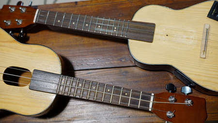 Ukulele guitar on a wooden table. 4 strings of voice used to deck playing music to relax