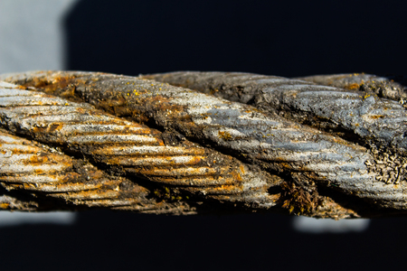 Thick steel rope close up. Bridge fence element. Detailed view. The surface of the steel cable is covered with rust and moss. Spring sunny day.
