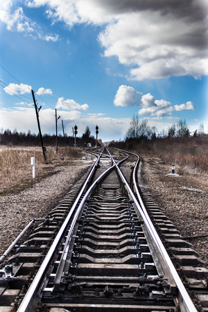 Railway bifurcation in north-west of russia in early spring. Blue sky with white clouds. A very cold windy day.