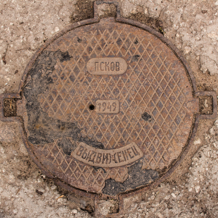 northwest: Old rusty cast-iron hatch-cover with inscriptions in Russian. Inscriptions from the top down read: Pskov is a provincial city in the north-west of Russia. 1949 - production year. Promoted worker - factory name. Partially covered with bitumen. Stock Photo