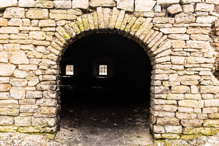 keystone light: Opening in the wall made in the form of an arch. Limestone carpentry walls.  A window with a lattice in the depths.