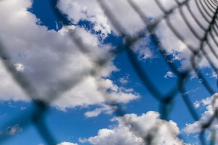 Background of Metal mesh fence against deep blue sky with white fluffy clouds backdrop. Concept of jail and freedom.