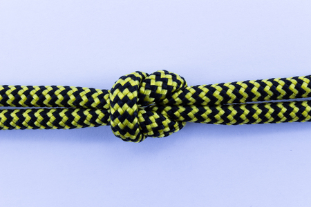 Two striped yellow and black ropes with knot isolated on white backfround