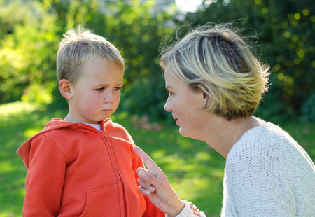 Mother scolds her son crying in the park Stock Photo
