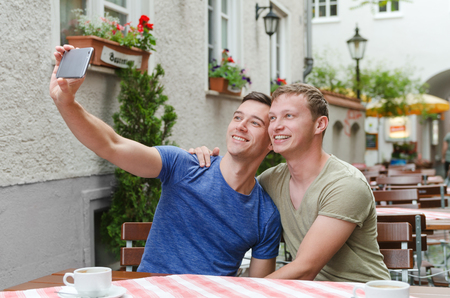 Shot of a young gay couple taking a selfie in a favorit cafe Stock Photo