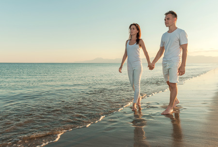 holding hands while walking: young couple holding hands while walking along the beach Stock Photo