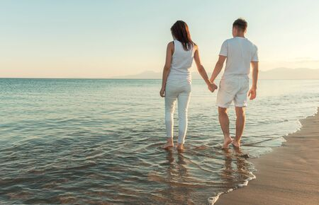 holding hands while walking: couple holding hands while walking in the water