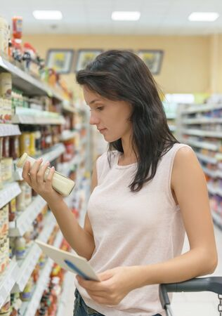 a jar stand: young woman standing in a grocery store aisle and looking at a product in glass jar Stock Photo