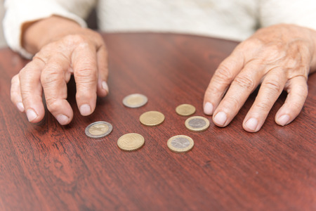 considers: shot of old women hands considers coins on the table