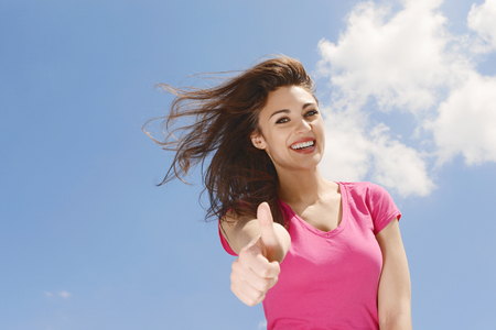 Portrait of an attractive young woman giving you a positive thumbs up on a background of sky