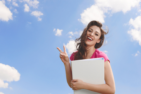 Portrait of an attractive young student with folder smiling brightly and  showing the peace sign on the sky background