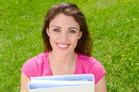 Cropped student smiling widely with folders in her arms on a background of grass Stock Photo