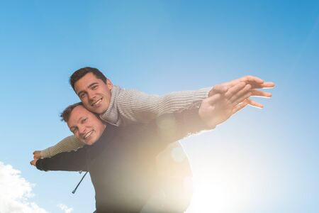 Homosexual couple fly with  his friend a piggyback ride on the sky background