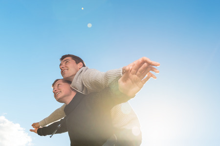 Homosexual couple giving piggyback ride, smiling outside. copyspace