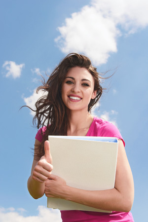 Portrait of an attractive young woman with folder smiling  brightly and giving you a thumbs up Stock Photo