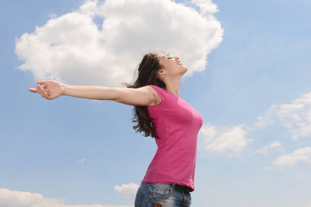 Pretty young woman with her arms raised while standing on a background of sky