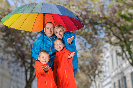 Colorful family, mother, father, son and daughter, have fun under rain