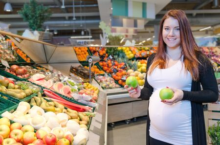 Pregnant woman with green apple choosing vegetables in supermarket Stock Photo