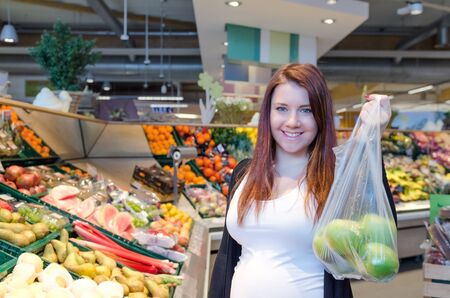 Pregnant woman with green apples in polybag hold in supermarket