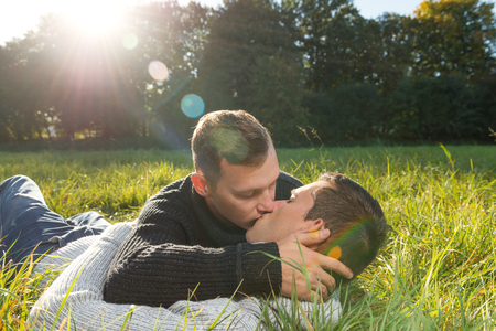 Shot of a kisses gay couple, lying at the grass  Stock Photo