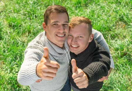 Young gay couple giving thumbs up  a top view Stock Photo