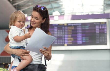 Young mother and her baby daughter at international airport, checking her e-tickets  for them  flight. Shot a below view Stock Photo